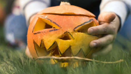 Ground angle shot. Close up of a childs hands putting carved pumpkin, jack-o-lantern, in the grass, in front of the camera