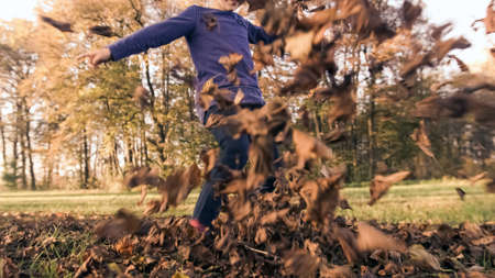 Ground angle shot of a caucasian preschool girl hitting, like a ball, heap of dry leaves into a camera, byciklist in the background 版權商用圖片