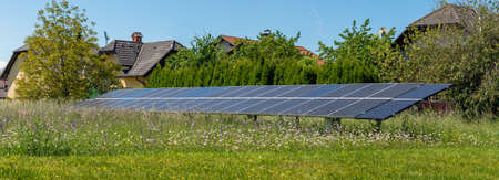 Solar panels on green meadow next to houses.
