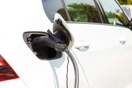 Charging an electric car with power supply cable.