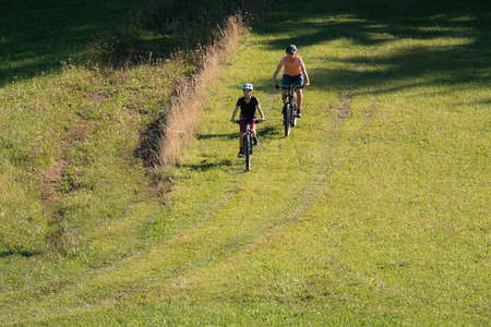 Two girls on mtb bikes. Mother and daughter riding on a trail.