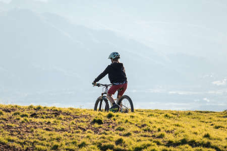 Girl child riding mountain bike at sunset. Beautiful golden summer light.