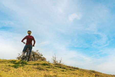 Woman on mountain bike looking at sunset in nature 版權商用圖片