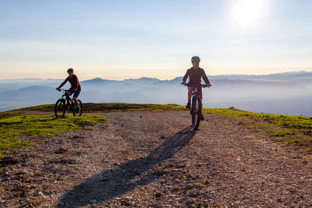 Mother and daughter cycling on mountain bikes at a sunset in mountains. 版權商用圖片