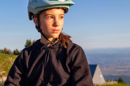 Girl child riding mountain bike into the sunset. Beautiful golden summer light. 版權商用圖片