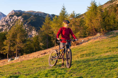 Woman walking uphill with mountain bike in nature on a beautiful day.