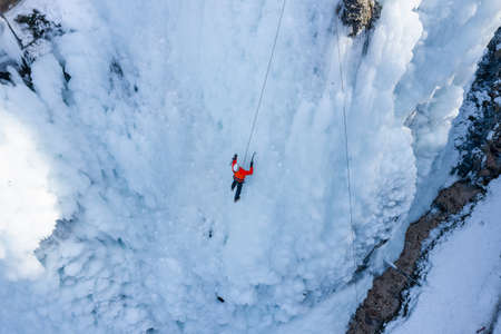 Man climbing on frozen waterfall by kicking with crampons into the ice and push up onto