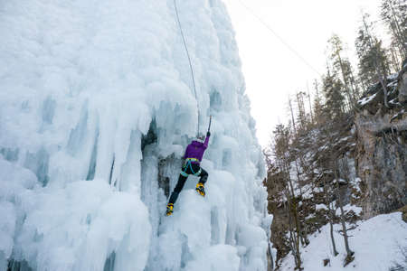 Alpinist woman with ice climbing equipment, axe and climbing ropes, climbing at a frozen waterfall, view from below