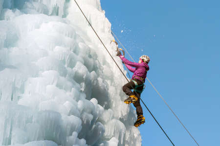 Female ice climber hiking a frozen waterfall, pushing axe pick into the slope and moving up to the top Stock Photo