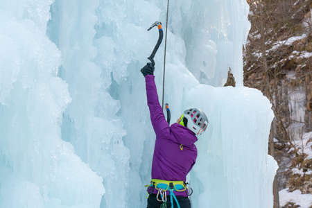 Female ice climber silhouette swinging ice axes on her way up vertical ice waterfall, side view 版權商用圖片