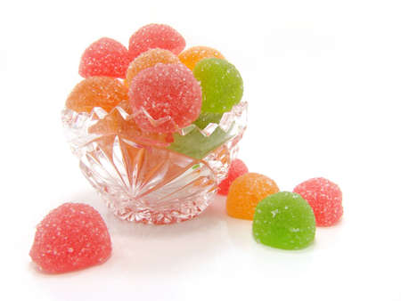 Colour fruit candy in a crystal vase on a white background                       photo