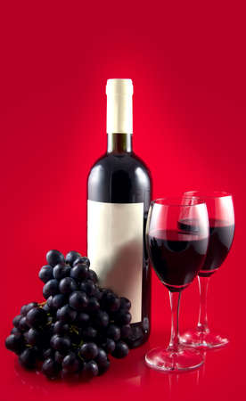 Two glasses with dark red wine on a red background. A dark wine bottle with a white label. Red ripe grape. Stock Photo