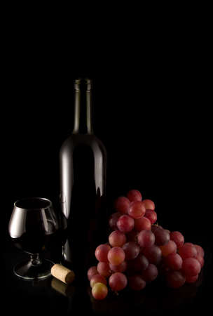 red grape and bottle of wine on black background with reflection Stock Photo