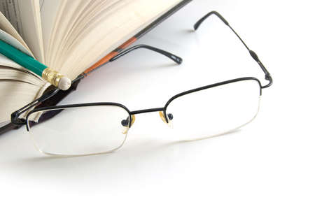 opened book with pencil and eraser and glasses