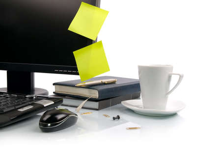 White cup of coffee and computer. Empty sticky notes on monitor.