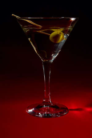 stiring: Martini cocktail with spanish olive and glass stiring stick. Dark red background