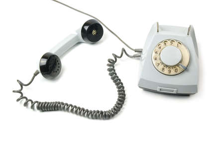 An old telephone with a rotary dial. White background.