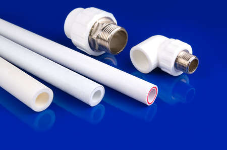 thermoplastic: White plastic fittings to use in hot and cold water supply lines. Blue background.