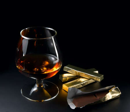 Cognac and chocolate on a black background. photo