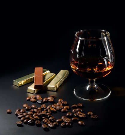 Cognac and coffe beans and chocolate on a black background.