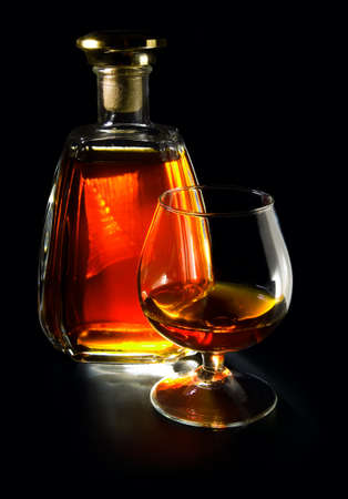 Bottle and glass with cognac on a black background