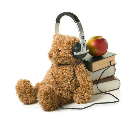 Teddybear with headphones on a white background. Concept of audiobook for children. Stock Photo