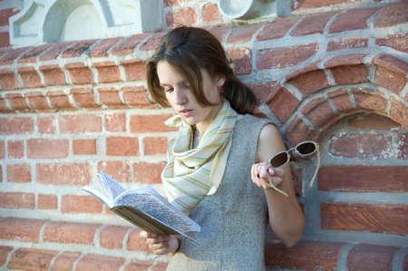 Pretty girl reading the book near bricks wall. photo