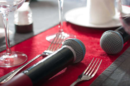 Microphone on the dining table. Concept of karaoke-restaurant. Blurred background.