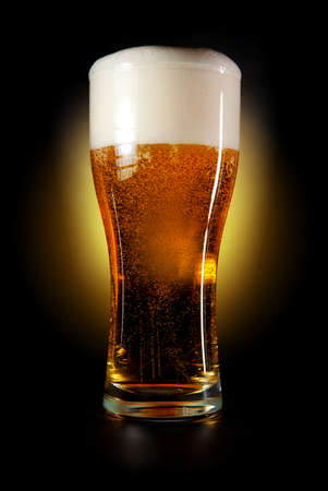 Pint glass of beer amber color with head on a black background   photo