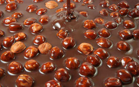 Chocolate flows on nuts  Tasty look - abstract food background Stock Photo
