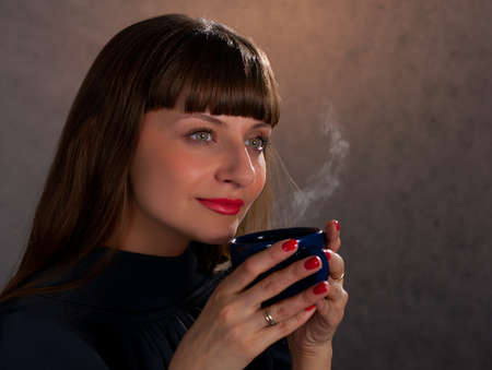 beautiful  woman drinking coffee on a dark background  Stock Photo