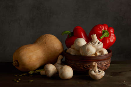 Rural still life of vegetables and glass jug. On a wooden table is onion and mushrooms Stock Photo