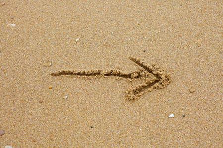 Drawn arrow on the sand