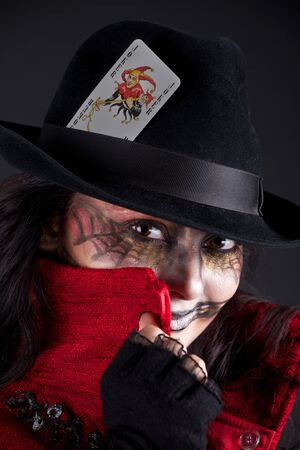 girl with a pattern on the face and playing card  photo