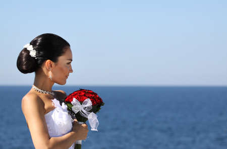 bride with beautiful red roses near the sea photo