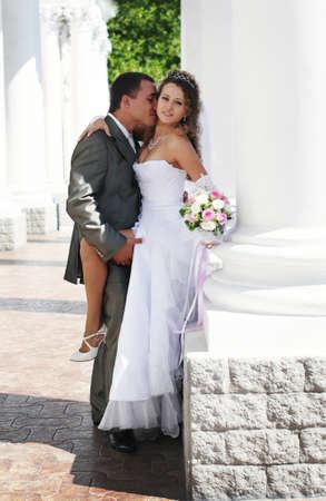bride and groom kissing near column photo