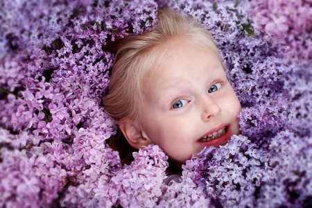 beautiful little girl with branch of lilac photo