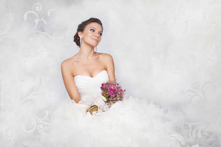 beautiful bride: Brunet bride portrait with flowers in studio Stock Photo