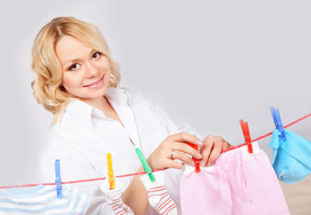 Woman hanging baby laundry to the rope photo