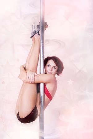 Girl making figure of poledance sport photo