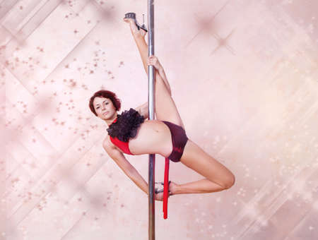 Girl making figure of poledance sport photo
