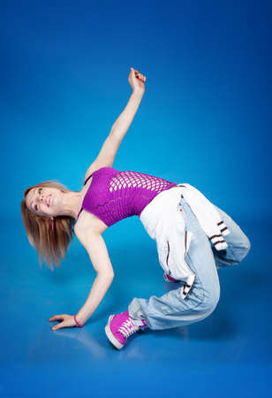 Beautiful girl dancing hip-hop isolated on blue background photo