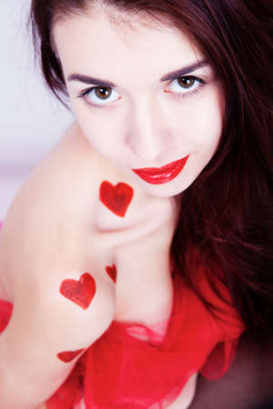 Brunette girl with red hearts isolated on white photo