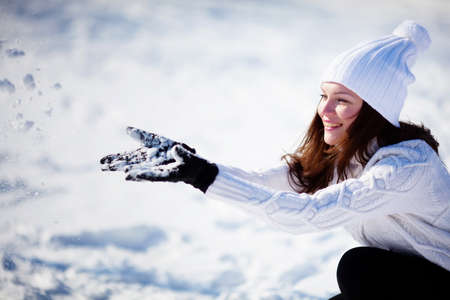 Girl playing with snow in park Stockfoto