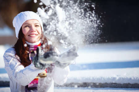 winter fashion: Girl playing with snow in park Stock Photo