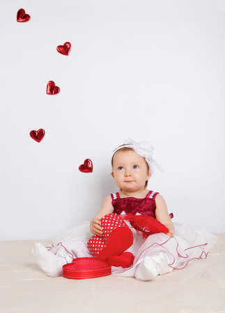Little girl with flying hearts in studio photo