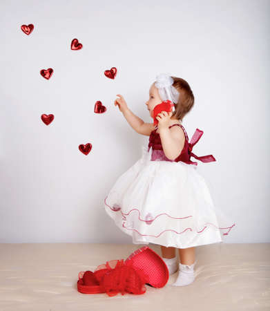 Little girl with flying hearts in studio