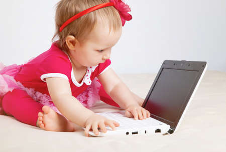 Little girl with laptop in studio photo