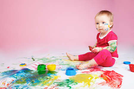 Child playing with color paints photo