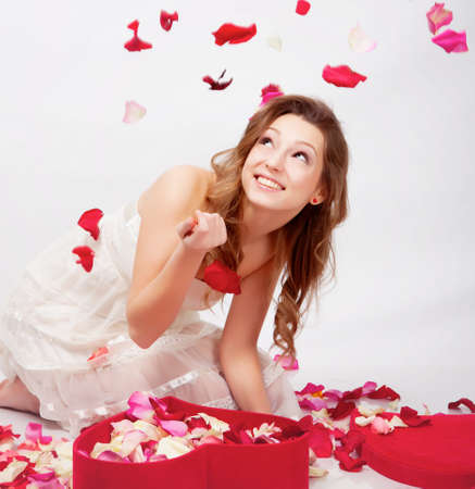 Beautiful girl with rose petals in heart form box photo